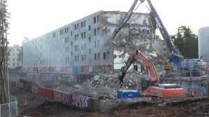 Deleten Volvo ottaa pihteihinsä talon päädyn. Käsittelyssä murskataan betonia, ja harjaterästä kertyy kasoittain. MIKKO RANTANEN